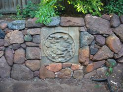 drystack stone retaining wall with Asian mural stone laid in the midst