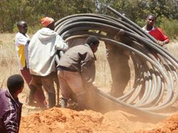 Secondary School students unrolling pipe prior to laying it in the 7 KM trench