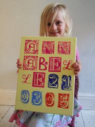 The little customer holding her girl's name and date of birth canvas