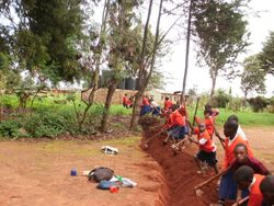 Primary School students dig the trench for the pipe to their school, near the water storage tanks.