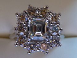 Platinum cluster with emerald cut center surrounded by 10 brilliant cut diamonds