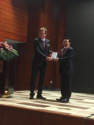 Prof Oliver Kaschke receiving the speaker's plaque from Prof Liangfa Liu