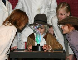 Lab workers (Zephyr Millington, Kaitlin Parker and Charlene VanLeuven) watch young Thomas Edison (Carolyn Waldee) create light.