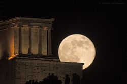 The full moon rises above Athena Nike temple at Acropolis in Athens