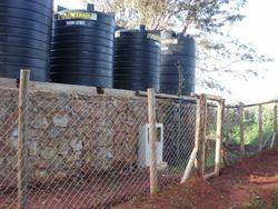 A fence surrounds the water storage platform. There are eight 5,000 liter plastic water tanks that are kept full by the incoming water.