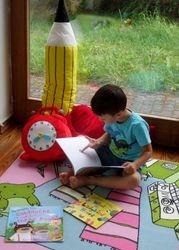 Notre coin lecture. La formatrice lit, pose des questions, l'enfant suit et répond. Un moment privilégié pour se détendre avant la fin du cours.
