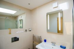 Large heated wall mirror in shower room