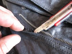 Start by using a blunt knife blade to cut old stitching