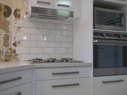New kitchen with subway tile splashback being installed. (photo 8).