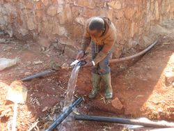 Moses preparing to install a T-fitting onto the main pipeline to feed the nearby faucet