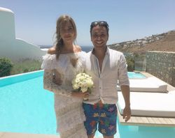 After the civil ceremony on July afternoon, the bride in  lace off-the-shoulder Alessandra Rich dress.with hair  styled in loose braid, accessorized with flowers