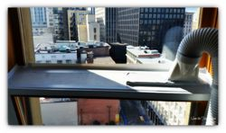 Portable ac exhaust vent installation on a hinged window