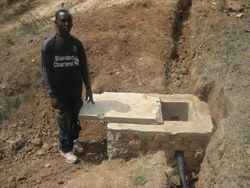 Moses showing a brick and concrete box that will hold an air valve in the pipeline.  This box was built in August-September 2011