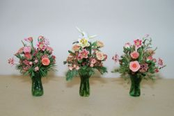 Roses and lilies in green glass vases