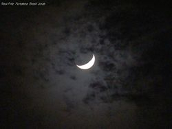 The crescent Moon behind thin cloud