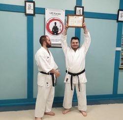 Sensei Richy lifting his award