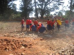 Primary School students help clear the ground near the water tank platform where the choirs will perform at the dedication