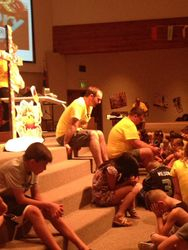 Pastor praying with VBS kids