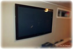"Wall mounted 62"" flat screen TV on a swiveling arm"