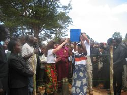 Mimi and Eric assist a second woman in placing the full water bucket on her head