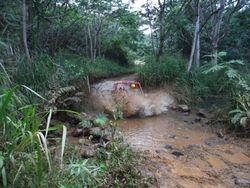 Driving through waterhole on ATV Adventure