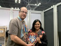 Alec Frazier and Diana Gabaldon Holding Fraser Coat of Arms During Interview for Autistic Reality Podcast