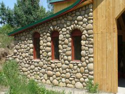 River rock Barn at Lonehawk Farm with wagon wheel windows and arches Longmont Boulder Colorado