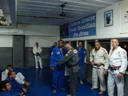 Master receiving Black Belt in Brazilian Jiu-Jitsu