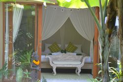 Relax on the day bed overlooking the pool and banana trees