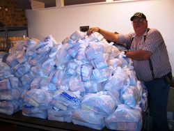 3-19-13 Volunteer Roland Klocker is dwarfed by pile of food