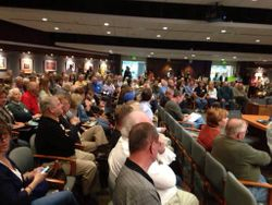 Packed room of hundreds opposing industrial mulch