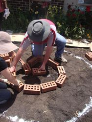 Laying the first bricks, then working them around to fit the right design