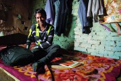 12 Vijay at home in Sanjay Camp slum. He lives in a one-room shack with his parents and his brother.  Their bed has no mattress and is made from old packing crates
