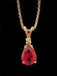 Pear cut ruby pendant in 14k yellow gold