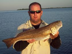 "Capt.Josh with a 8.9 lb 27"" redfish."