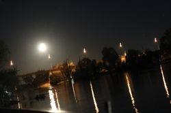 Full moon coming up over bridge