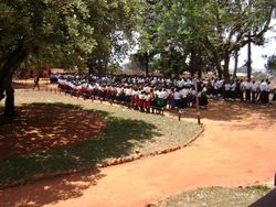 The Primary School students prepare to join the large procession from the Mission House to the water tank platform