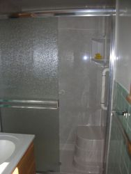 After: Seated Shower w/Silver White Marble walls & new doors.