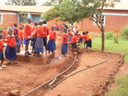 Primary School students dig the trench for the pipe to their school, near the end of the pipe at their school.