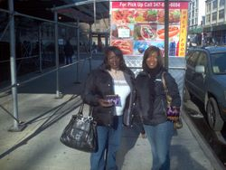 Courtney & Patricia posing in front of a food vendor in Q