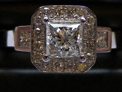 18ct White gold princess cut center diamond, surrounded by pave set brilliant cut with princess cut shoulders