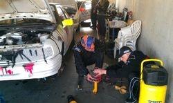 Marcel en Danny hard aan het werk om de schokdemper te vervangen