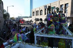Krewe members ducking street lights during the parade
