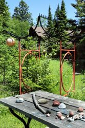 Hansen ornamental arbor from Mom and rocks collected by visitors.  Table first thing Gary built when we were still just tenting.