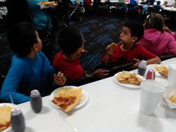 Children enjoy pizza, chips cake and drinks