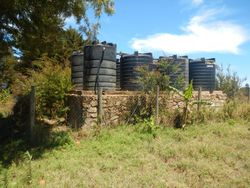 The eight 5,000 liter water storage tanks have a fence around them.  Trees and bushes are allowed to grow next to the tanks to provide shade for the plastic tanks and to discourage curious people.