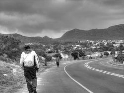 A man walking by the side of the road