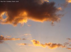 Colored small clouds and crepuscular rays at sunset