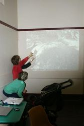 Kids making shadow birds on a photo of a Malleefowl mound