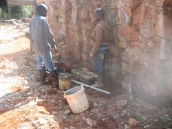 Moses building the brick and concrete frame for the dedication plaque on the water storage platform